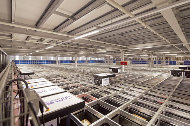Wheeled robots drive along an overhead grid to pick up products from storage bins at Rhenus Logistics' facility in Tilburg, Netherlands.