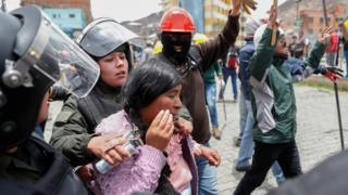 Members of the security forces detain a woman during clashes between supporters of Evo Morales and opposition supporters in La Paz, Bolivia, 11 November, 2019.