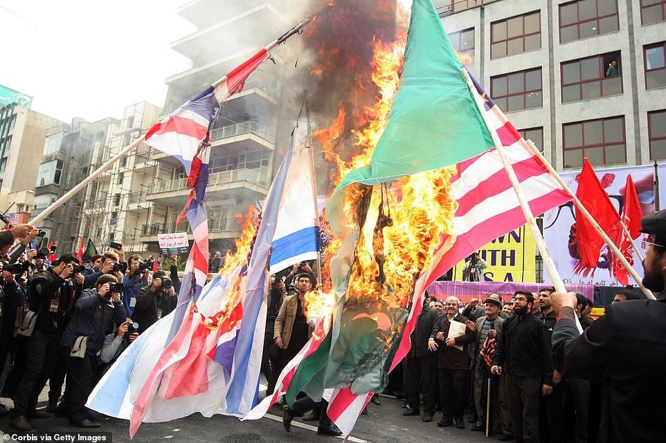 Here some protesters are burning flags from the UK, Israel, Saudi Arabia and the United States during an annual demonstration to mark the anniversary of the birth of the Iranian revolution