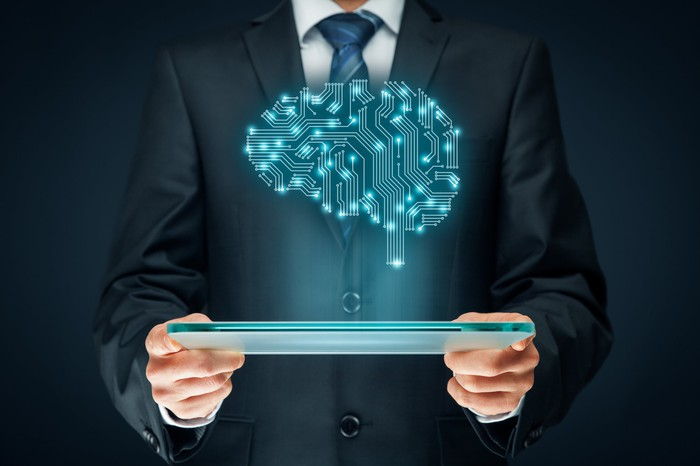 A brain illustrated with electrical connections hovering above a tablet, signifying artificial intelligence.