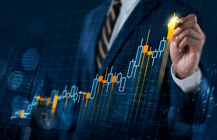 A stock graph moving higher with a man in a suit clicking on it