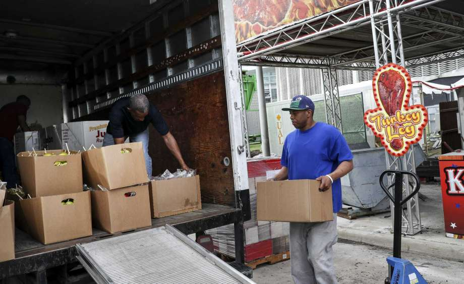"""Aaron Heller, from right, a warehouse worker for the Star of Hope, Thomas Tousant, who described his job as a """"servant of God,"""" and Larry Reynolds, a transportation specialist, load food that was donated to the Star of Hope on Friday, March 13, 2020, near NRG Stadium in Houston. Vendors from the Houston Livestock Show and Rodeo donated unused food to local charities, including the Houston Food Bank and the Star of Hope, after the rodeo was canceled due to concerns about COVID-19. Photo: Jon Shapley, Staff Photographer / © 2020 Houston Chronicle"""