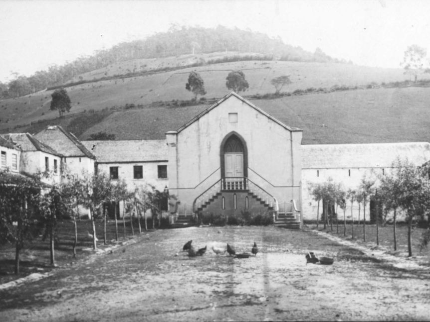 An historic black and white photo of a large sandstone building with a steep hill in the background and chickens in foreground.