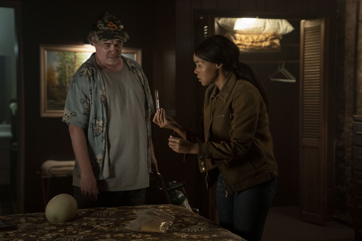 Janelle Monáe examines a small object in her hand in a dingy hotel room in season 2 of Homecoming season 2.