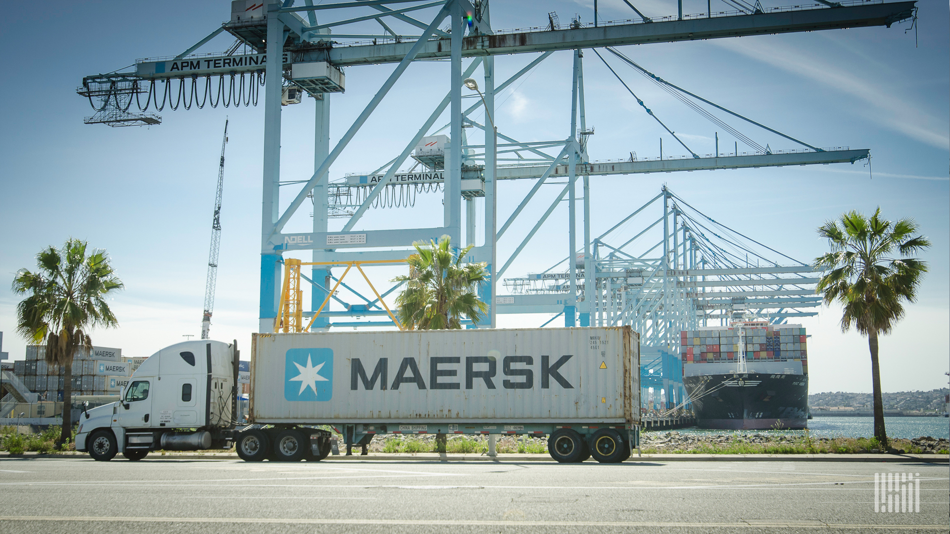 A truck carrying a Maersk container is in front of a number of cranes used to load/unload cargo ships.