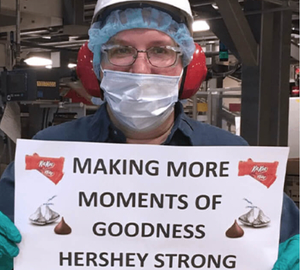 Worker holding sign: Making more moments of goodness Hershey strong