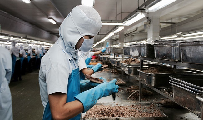 A worker in a production line at a seafood processing operation in Bangkok, Thailand, in April 2020.