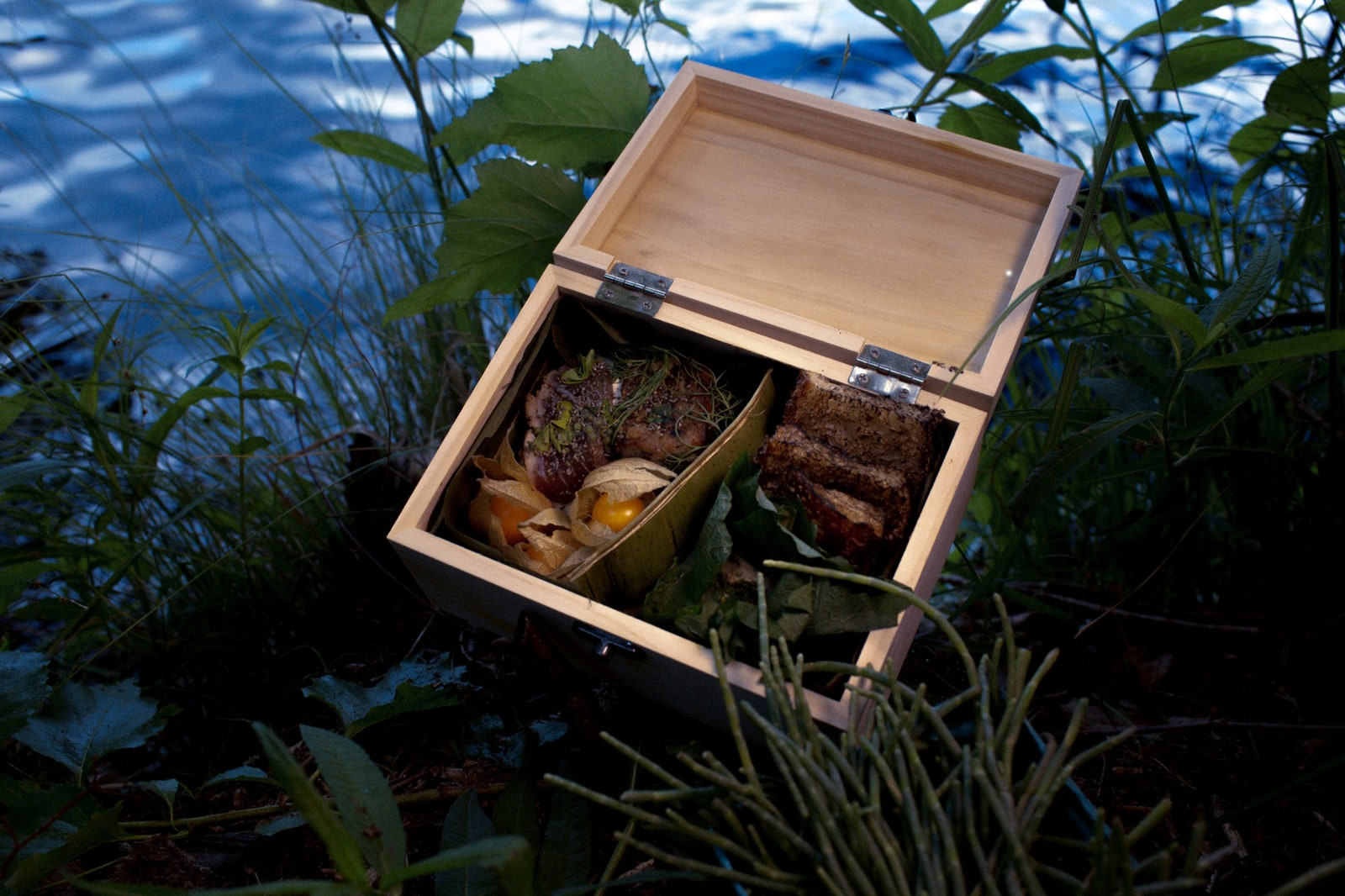 Wooden box with ingredients by body of water.