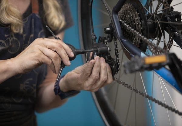 A woman uses a bike chain tool.