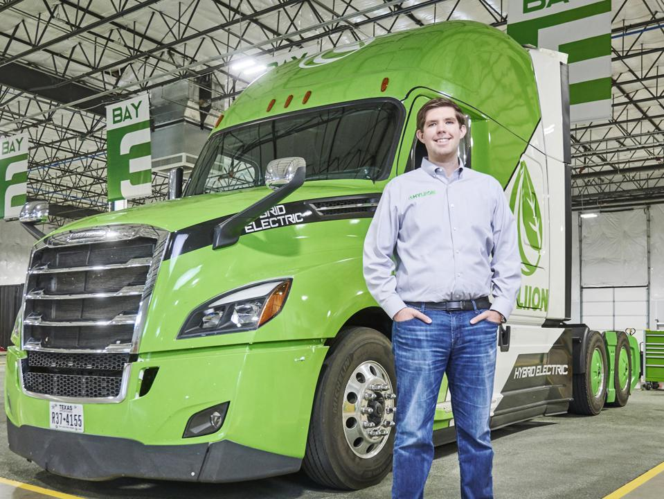 Hyliion CEO Thomas Healy stands with electric truck.
