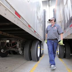 Dusty Senn, Associated Foods truck driver, walks between two trailers after hooking up a set of trailers outside of the Associated Foods distribution warehouse in Farr West, Weber County, on Wednesday, Aug. 19, 2020.