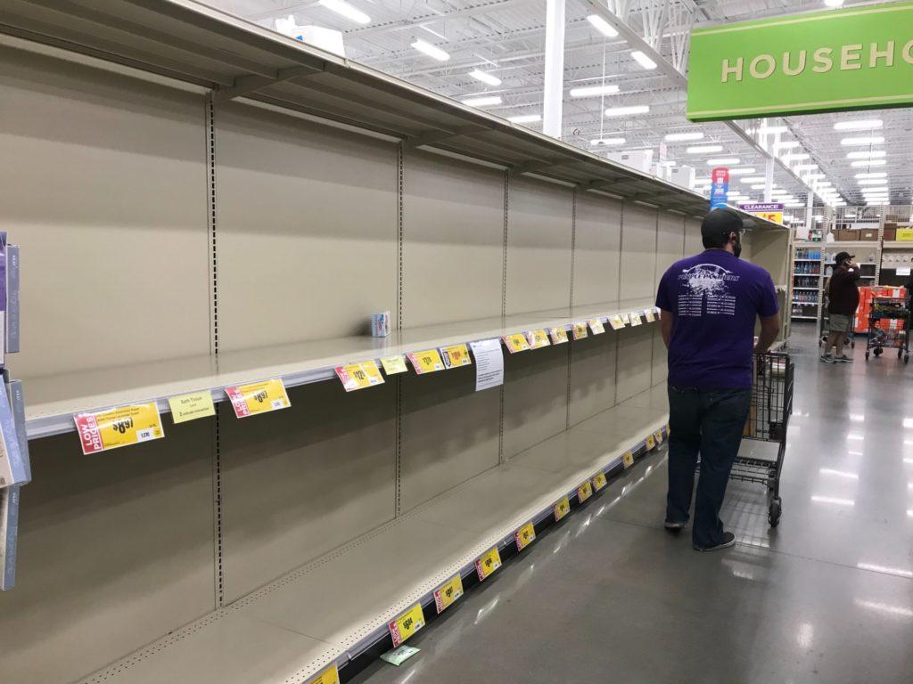 man pushing shopping cart past empty store shelves
