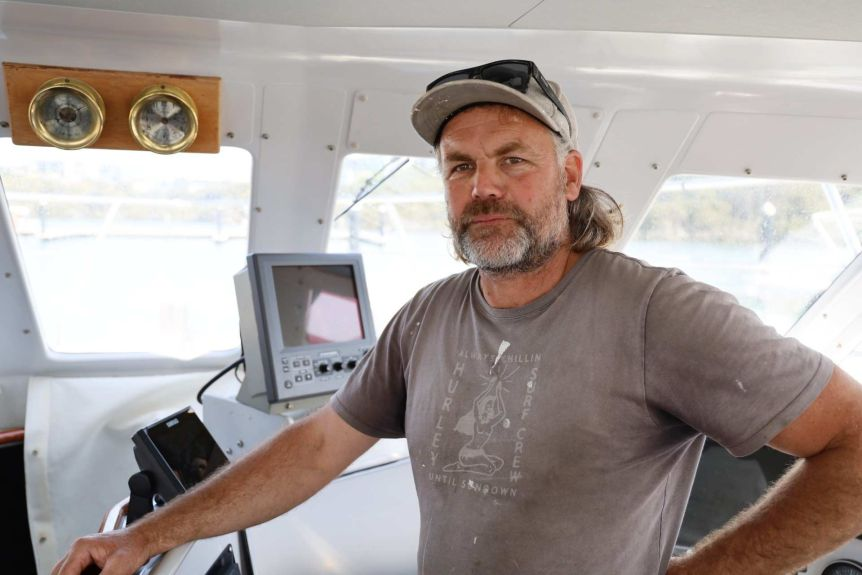 A man wearing a grey hat and a grey t-shirt stands next to navigation instruments inside a boat
