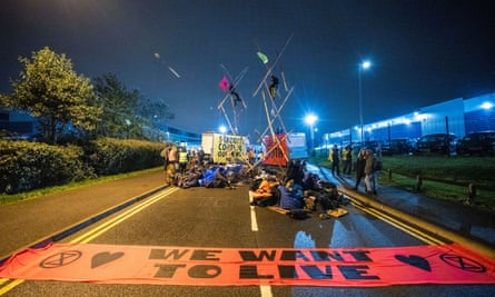 Scene of a road blocked by protesters and vans at night, with a large orange banner saying 'We Want To Live' spread out on the road.