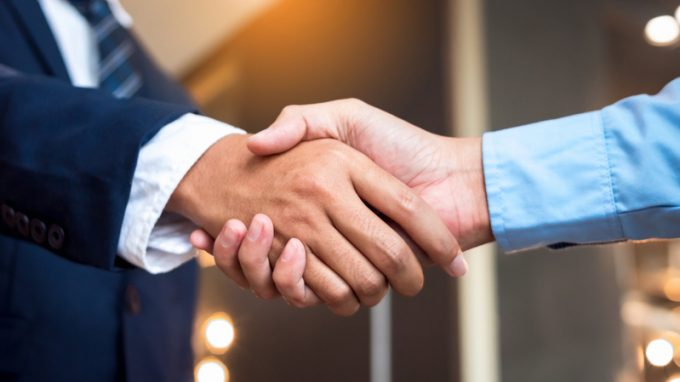 Close up businessmen shaking hands during a meeting. Handshake deal business corporate.