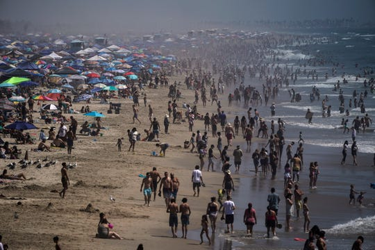 People crowd the beach in Huntington Beach, Calif., on Labor Day weekend, seeking relief from a dangerous and record-setting heatwave but risking the spread of coronavirus.