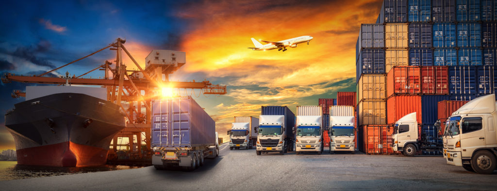 picture of a container ship being offloaded with trucks in the center and a plane overhead