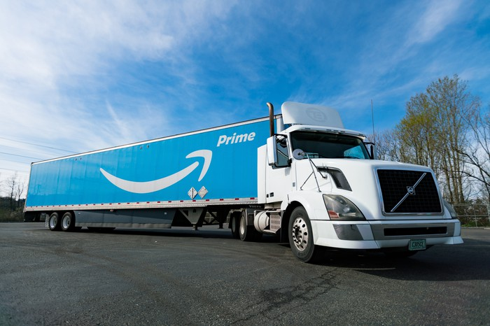 An Amazon truck with a white cab and a Prime logo on its side, under a sunny sky.