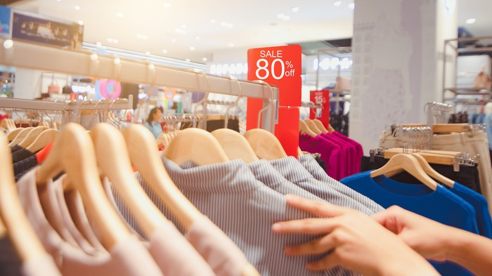 A clothing rack featuring items at 80% off in a sale.