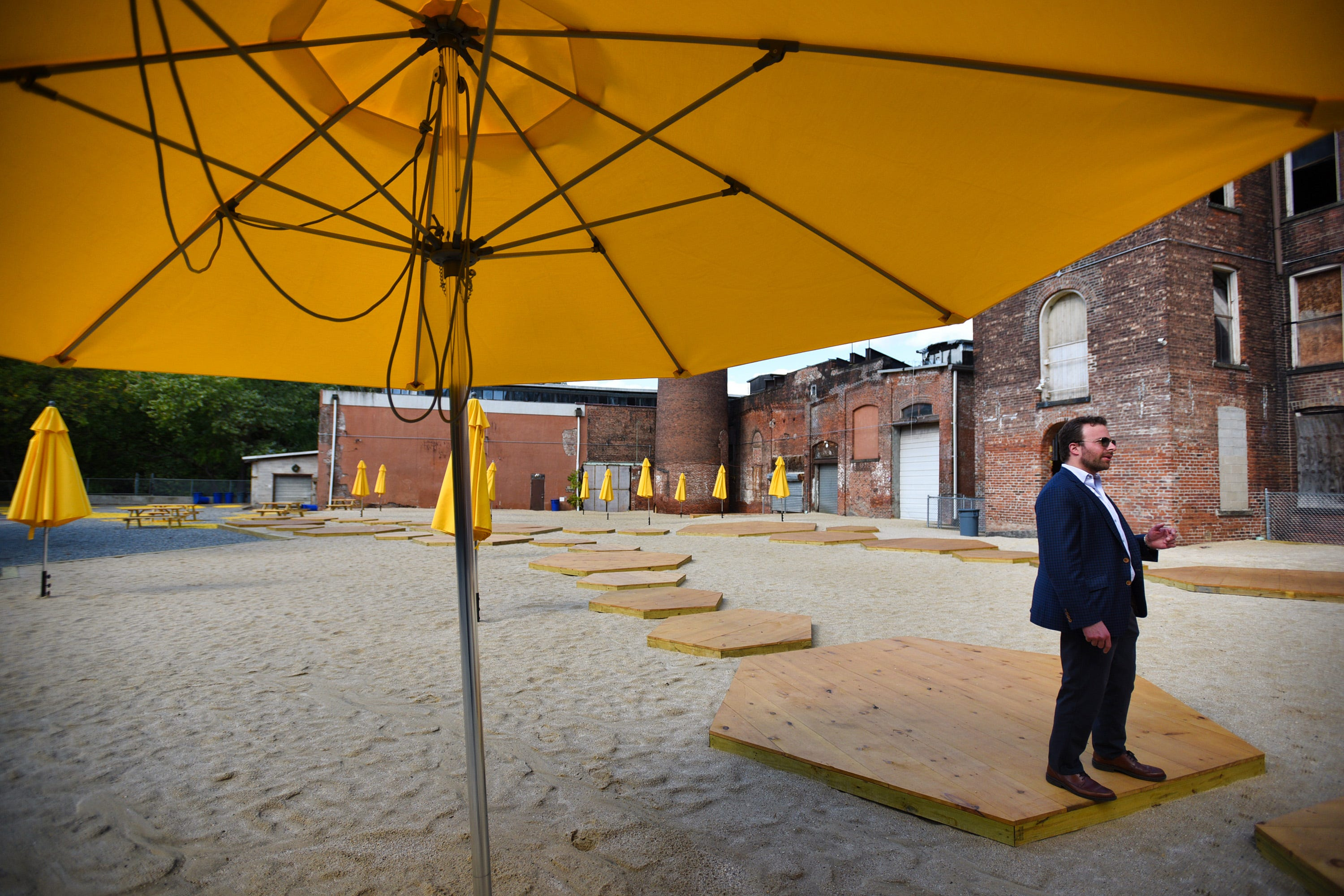 Levi Kelman, CEO of Blue Onyx Companies, who bought a complex of old mill buildings near the Passaic River for $4.2 million located in Paterson, walks on platforms across a sand-like beach while showing around the sites, photographed on September 30,2020.