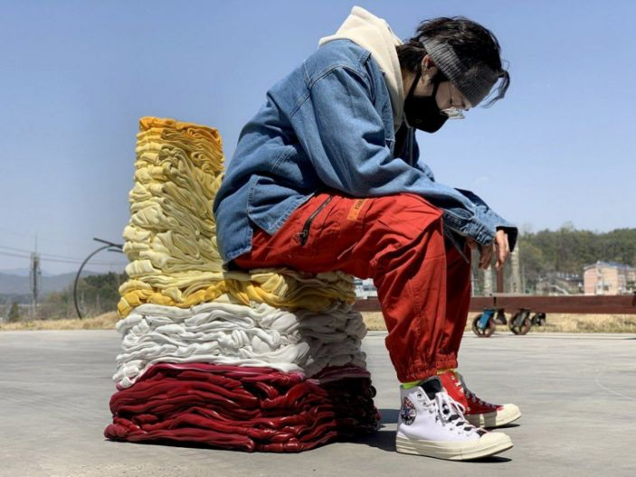 Artist Youngmin Kang sits on one of his sculptural repurposed chairs.