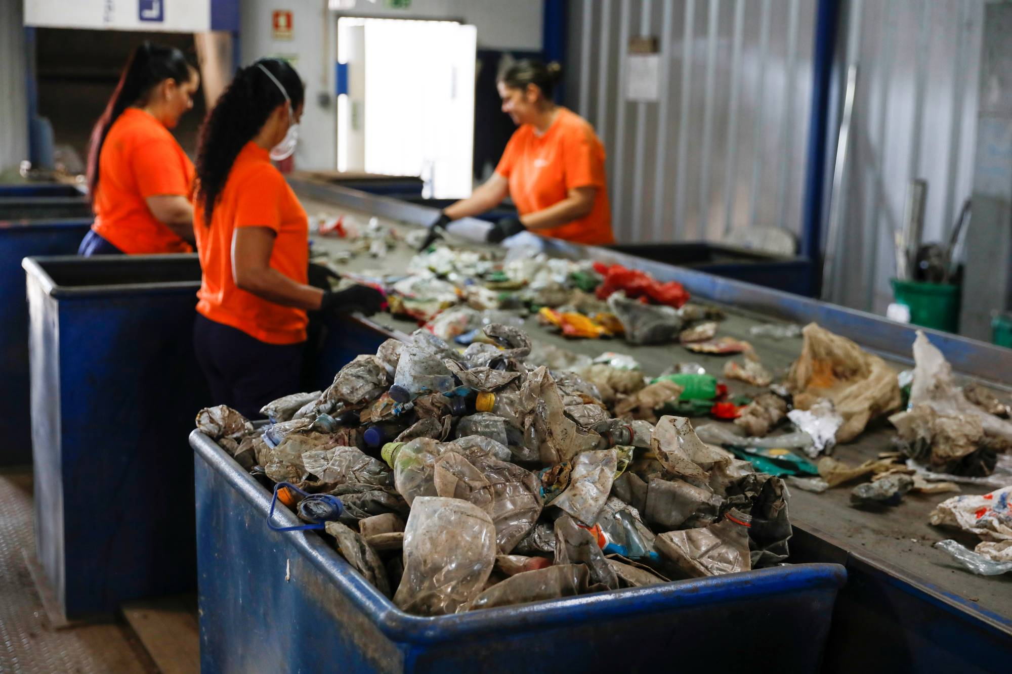 Workers separate different types of plastic at an Extruplas plant in Seixal, Portugal.   REUTERS