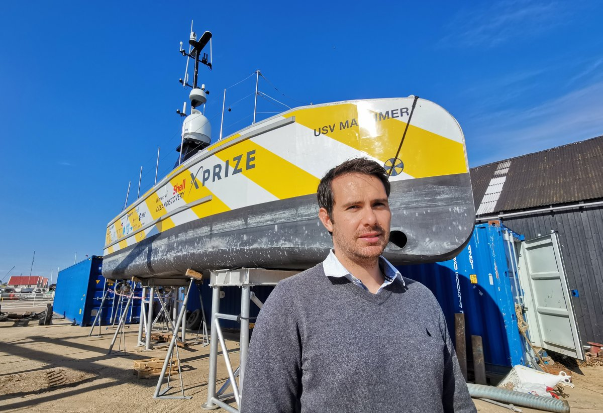 Neil Tinmouth, Sea-Kit International's chief operating officer, standing beside the USV Maxlimer at the company's headquarters in Tollesbury, England.