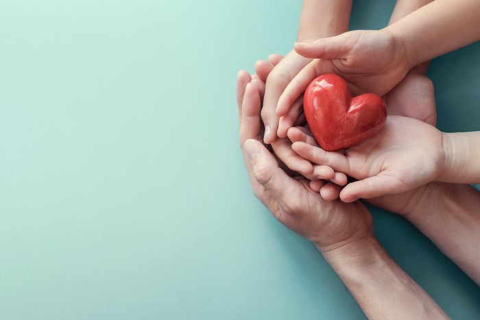 Several hands hold a red heart.