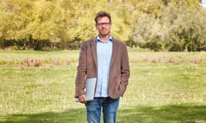 James Suzman holding a laptop and standing in a field