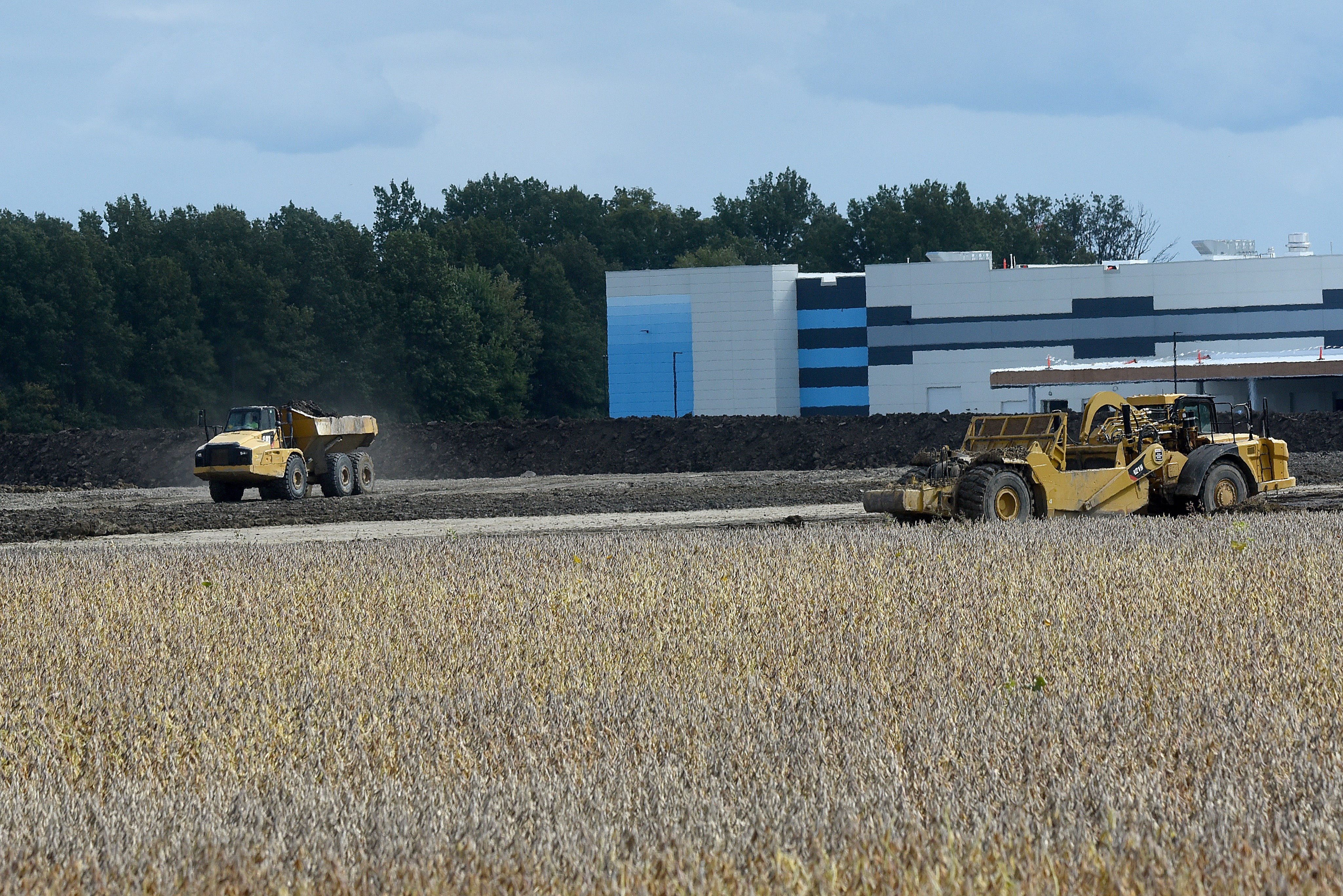 Heavy construction equipment works to lay the groundwork for a huge warehouse along Mink Street in Etna Township, alongside the new Amazon Distribution Center in the background.
