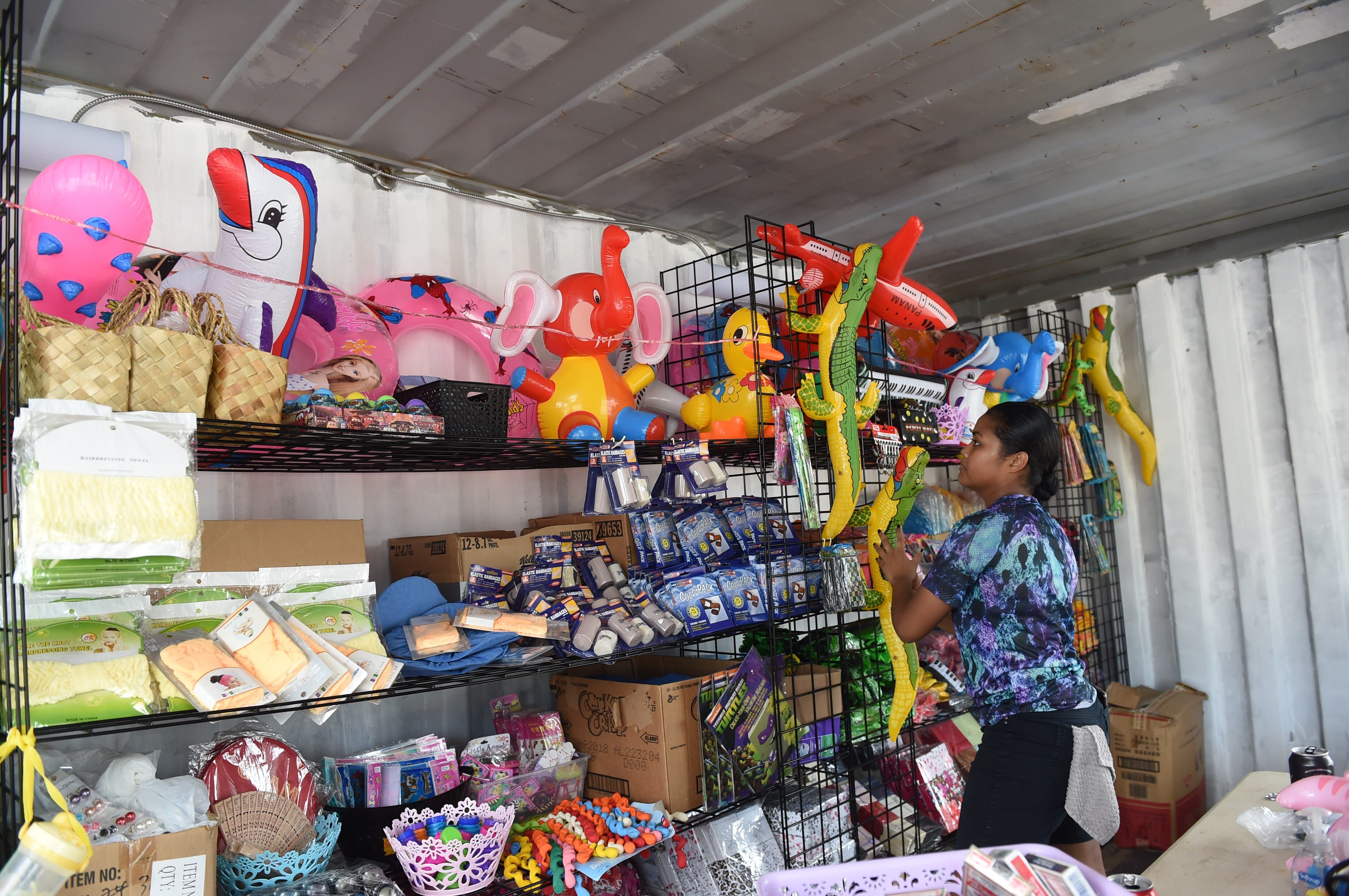 """Volunteer Cassandra Towai organizes prizes at the """"Spin-to-win"""" game booth in preparation for the opening of the 75th Liberation Carnival at Paseo de Susana Park in Hagåtña in this June 9, 2019, file photo. An audit of the 75th Guam Island Fair and Liberation Day Carnival found it didn't comply with Guam procurement rules and regulations."""