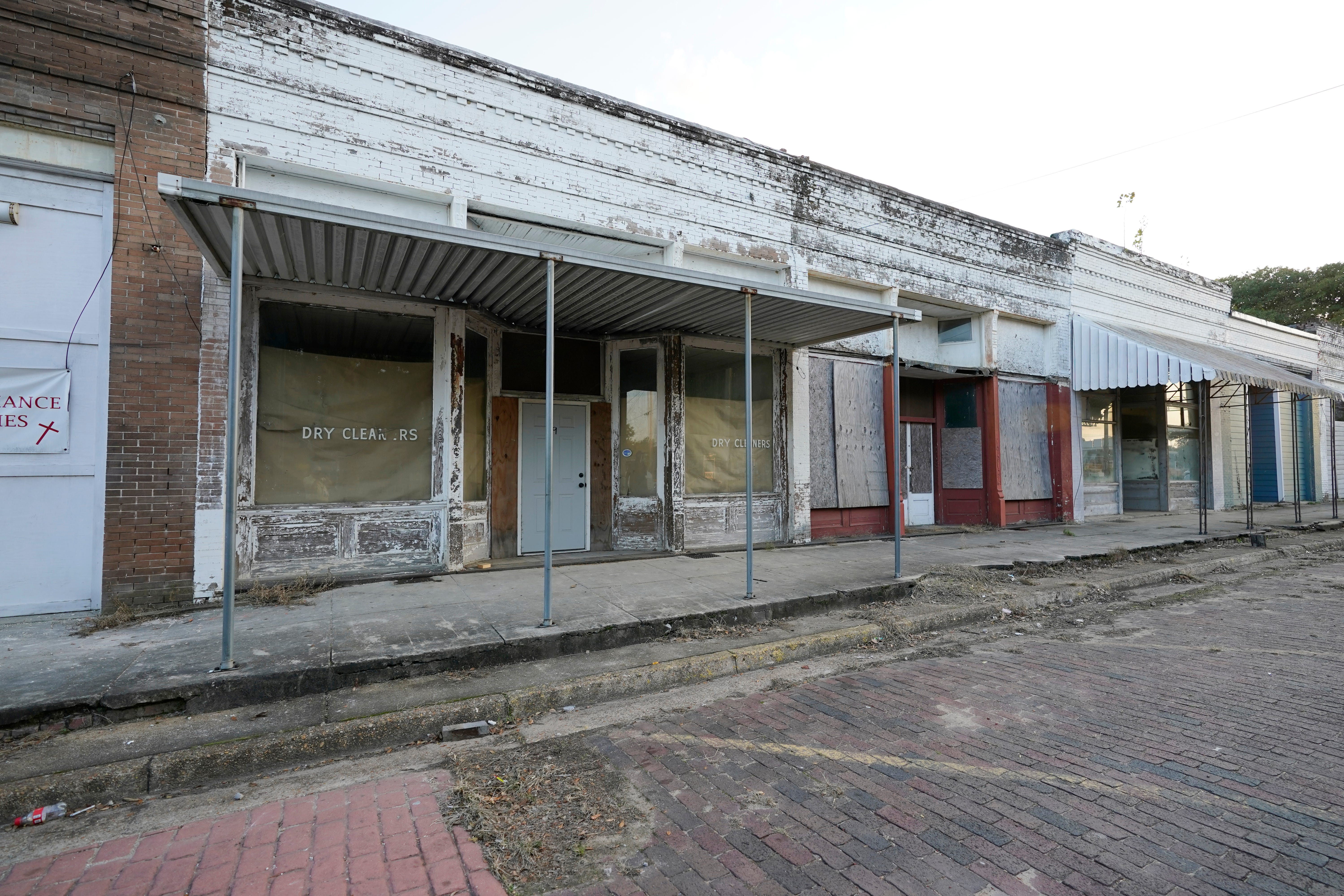 Vacant, unkept, boarded up and weather worn store fronts line a street in downtown Itta Bena, Miss., Thursday, Oct. 22, 2020. Area residents believe the high price of electricity provided by the city as one of the reasons for store closures. (AP Photo/Rogelio V. Solis)