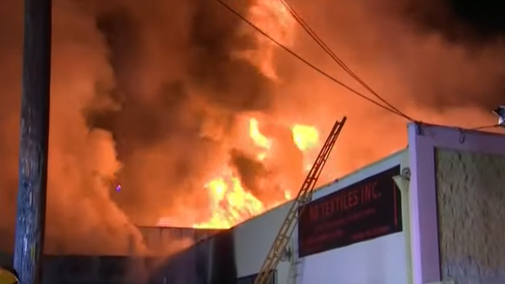 Los Angeles firefighters battle a massive fire that spread to two buildings in the city's Garment District on Tuesday.