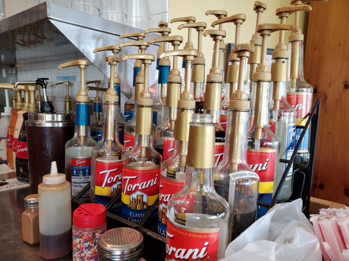 Close-up of rows of Torani syrups, used to flavor Italian sodas or other beverages, in a coffee shop.