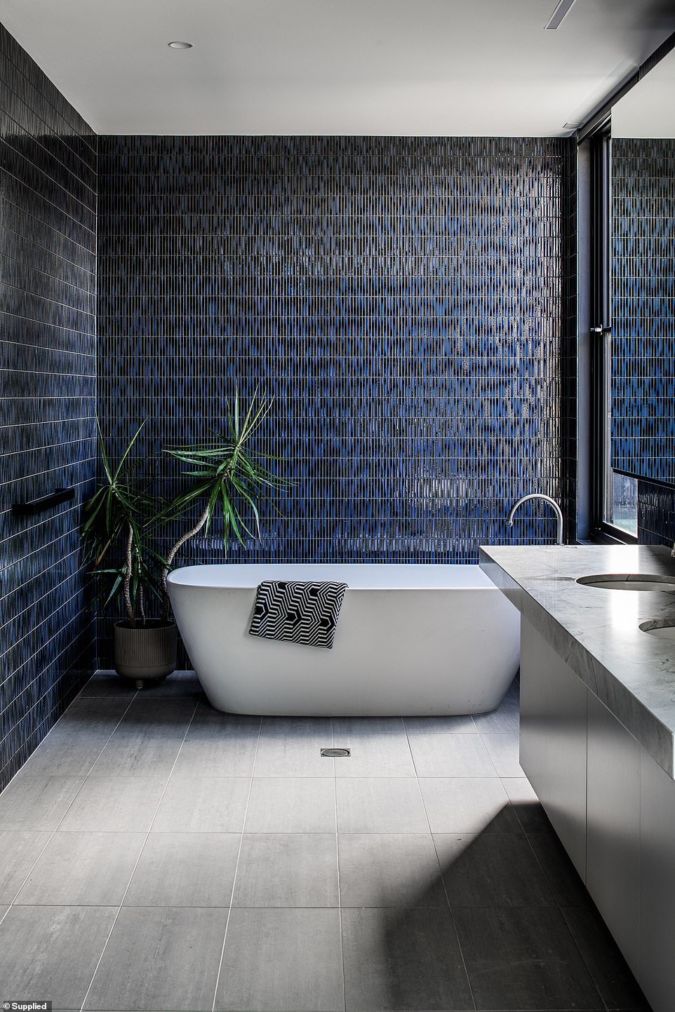 Japanese finger tiles run from floor to ceiling in the bathroom, which has a freestanding bathtub and 'his' and 'hers' sinks