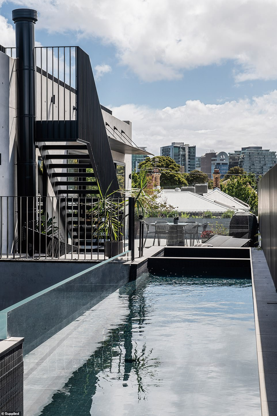 The standout feature is undoubtedly the suspended swimming pool that spans the space between two outdoor terraces