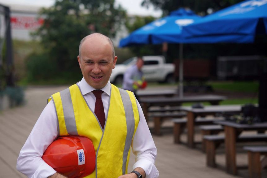A bald man wearing a hi-vis vest over a shirt and tie holds a hard hat in the crook of his arm.