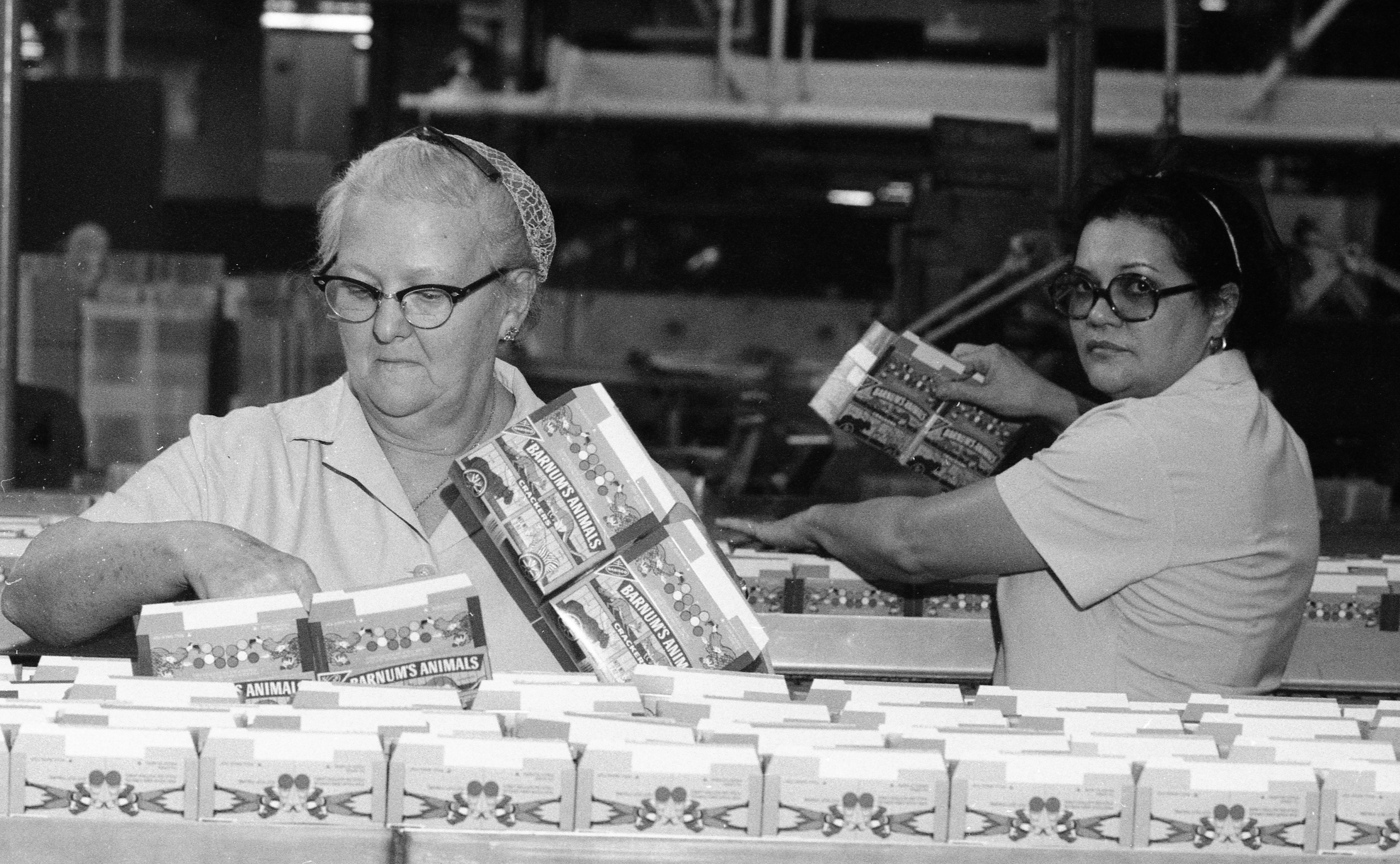 Two workers watch over the line of boxes which will shortly contain Barnum's Animal Cracker cookies at the Nabisco manufacturing plant on Route 208 in Fair Lawn, N.J., on November 3, 1977.