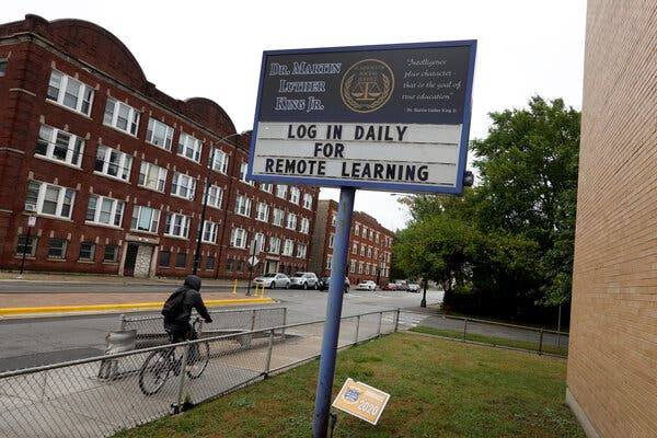 In Chicago, a sign in front of a school encouraged students to participate in remote learning in September, but now the city is talking about getting kids back into classrooms.