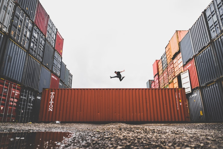 man jumping on container