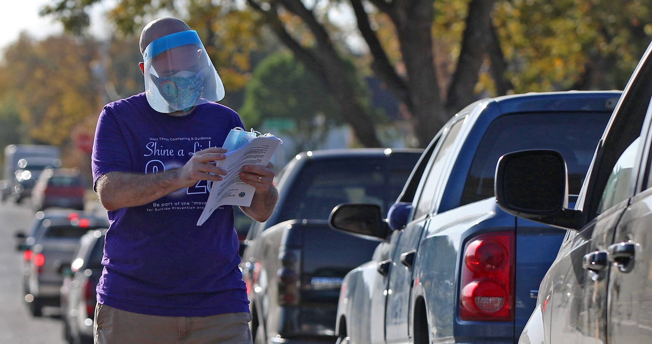 Pastor Timothy Davenport-Herbst directs traffic during a food distribution event at the St. Paul Presbyterian Church on Saturday, Nov. 21, 2020.