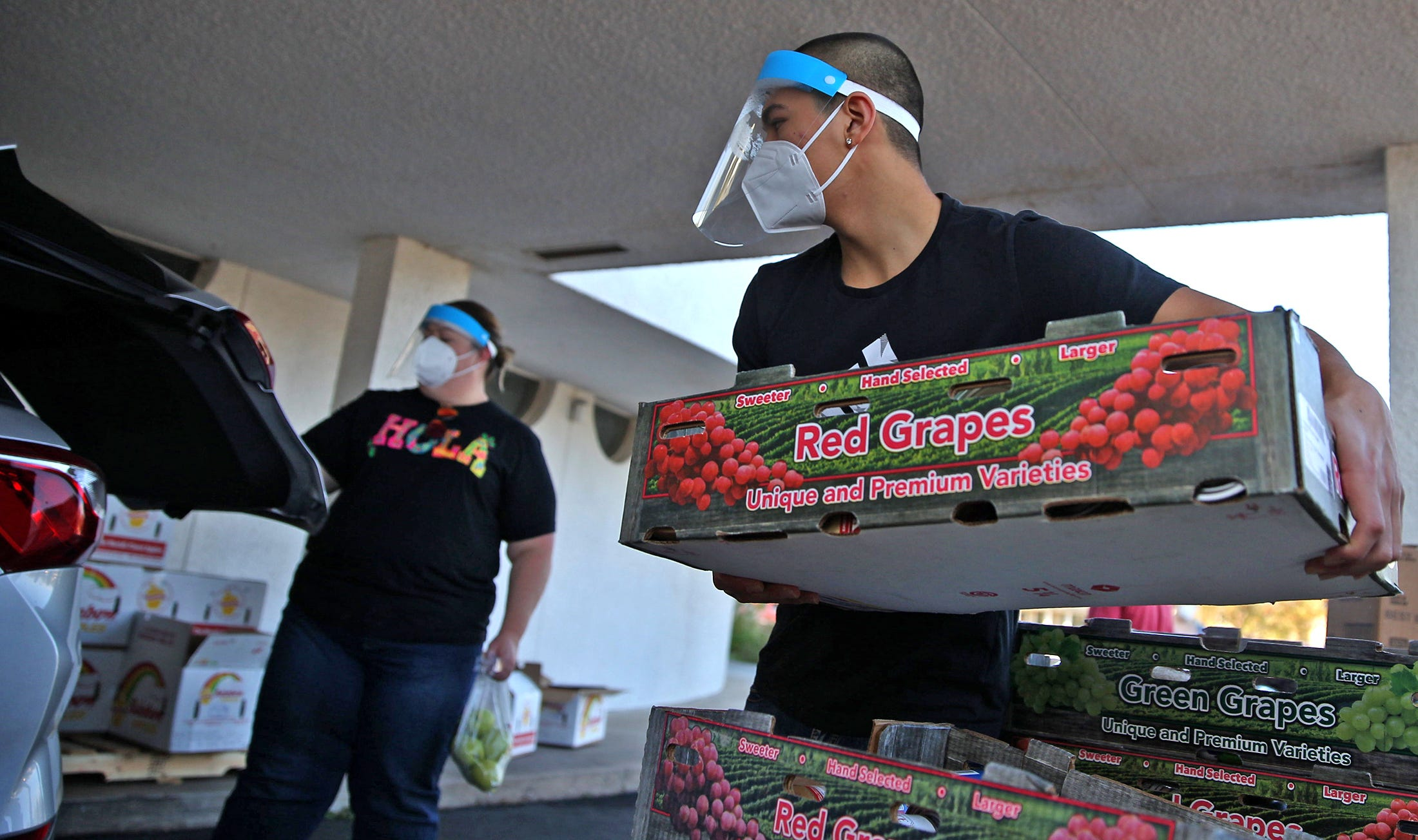 Eli Calderon, center, loads food into vehicles during a food distribution event at the St. Paul Presbyterian Church on Saturday, Nov. 21, 2020.