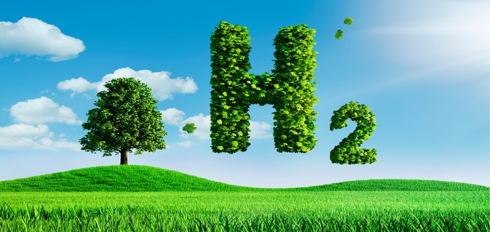 Composed of green leaves, the symbol for hydrogen floats over a green field.