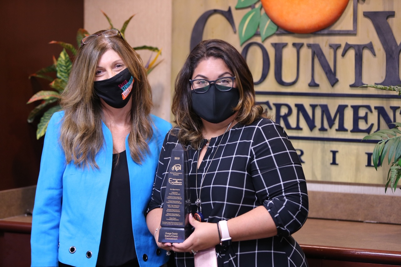 Two women holding an award