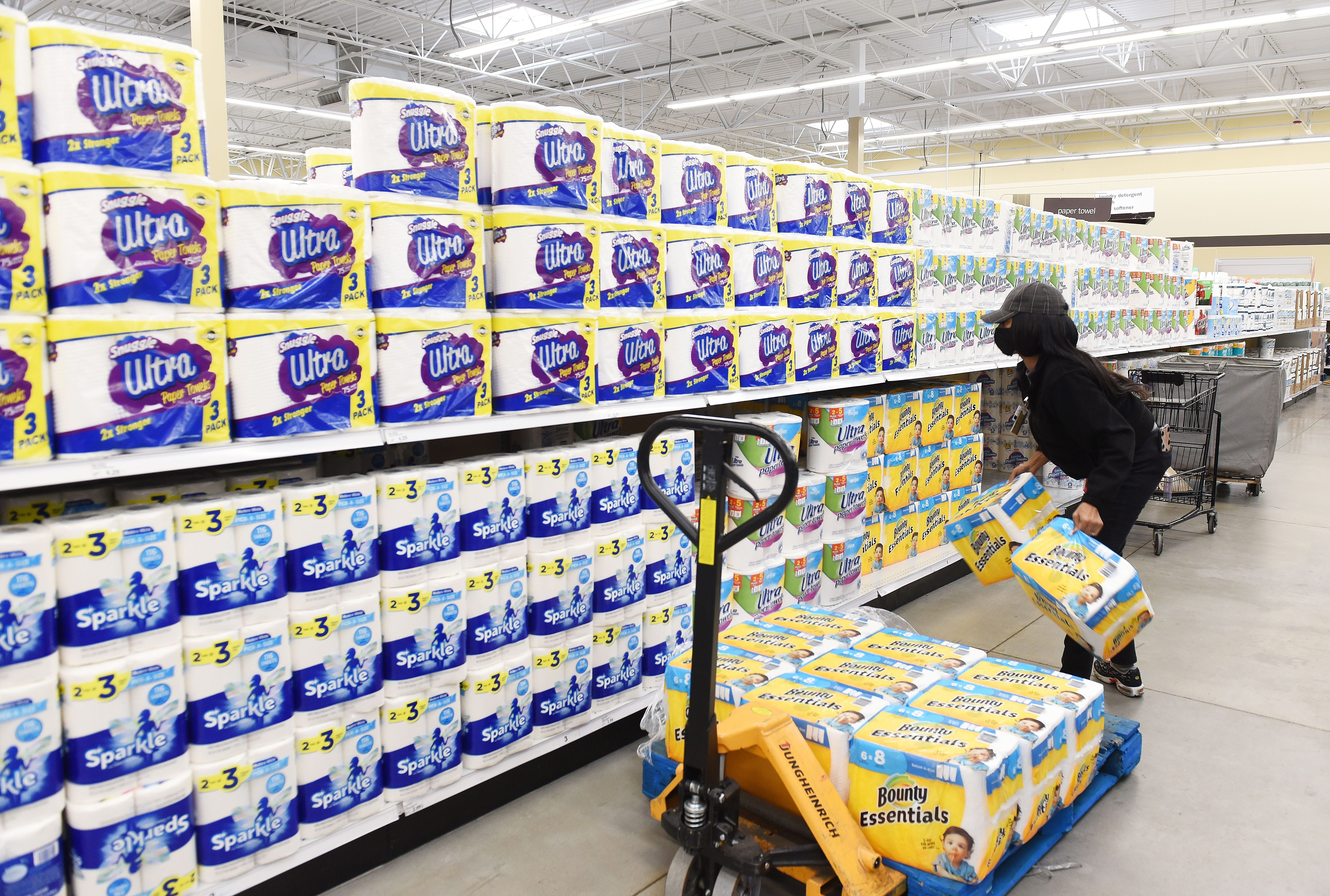 An employee at Meijer in Detroit restocks store shelves with paper products.