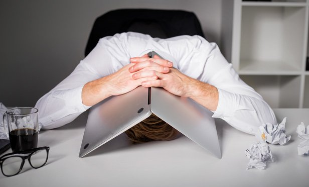 Frustrated businessman hiding under laptop during online trading outage