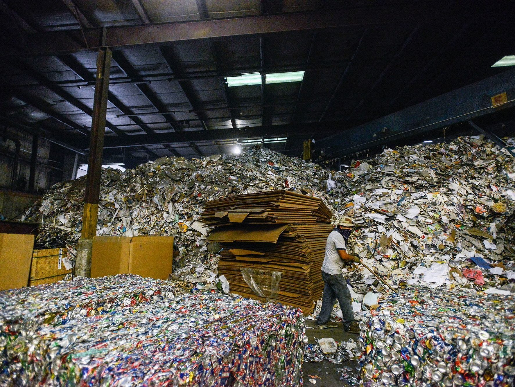In this file photo, Jose Ramos pushes crushed cans off the floor inside the Curbside Management recycling center in Woodfin. Curbside Management, or Curbie, handles recycling for the city of Asheville and its 30,000 customers, as well as for Fletcher, Woodfin and Weaverville.
