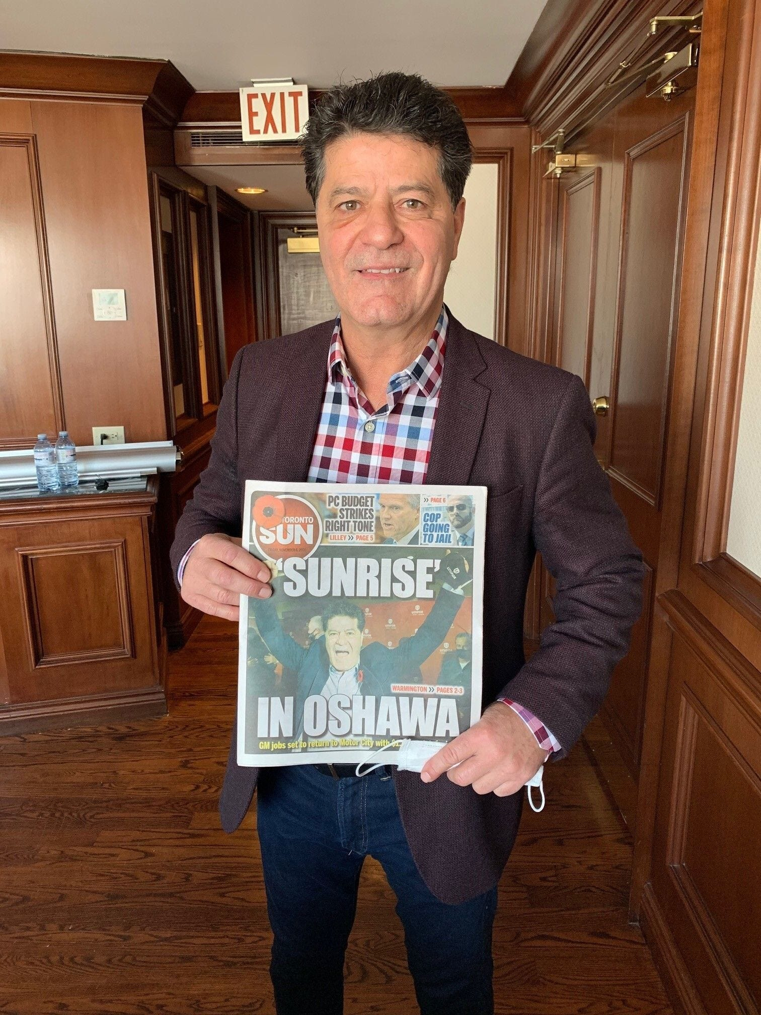 """Unifor National President Jerry Dias displays the front page of the Toronto Sun newspaper with the headline """"'Sunrise' in Oshawa"""" on Nov. 6. Unifor got General Motors to reallocate product to Oshawa to restart the assembly lines after GM had said it would idle vehicle production there."""