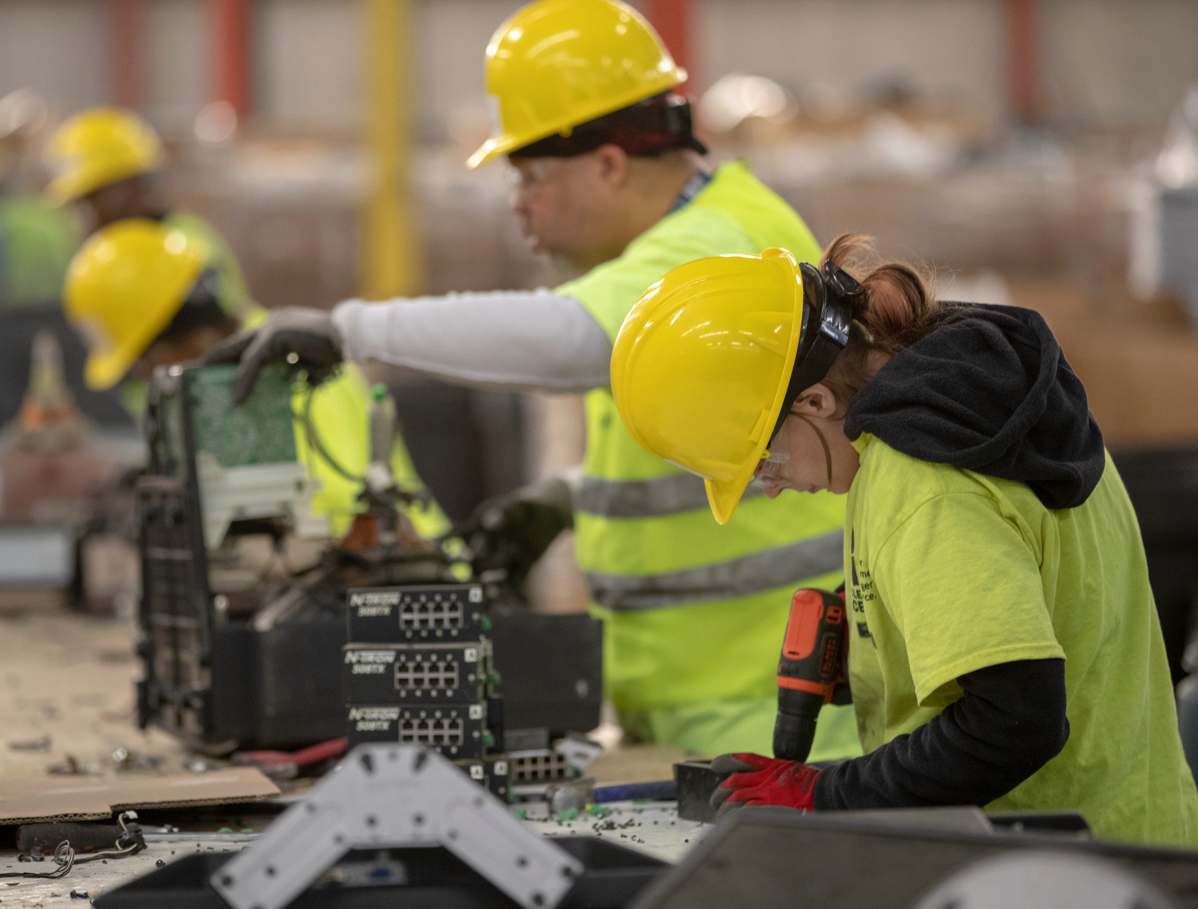 Workers use tools to separate items at Recycle Force, Wednesday, Jan. 8, 2020.
