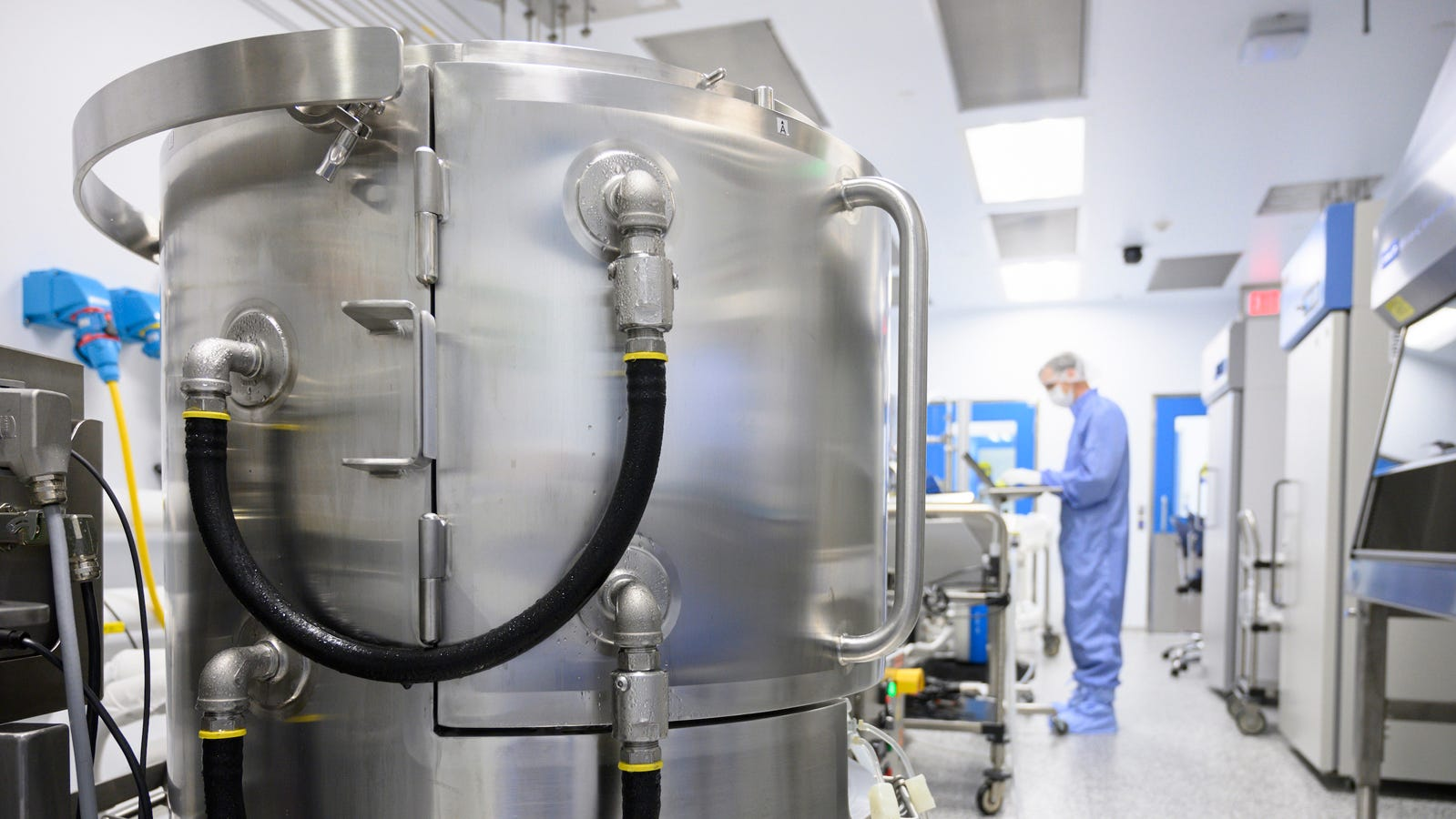 A Lonza Biologics employee in Portsmouth enters data on the other side of a mixer used in the production of the mRNA-1273 vaccine Moderna developed to fight the COVID-19 virus.